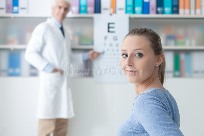Exam with an eye doctor. Young women in the optometrist office examining her eyesight, he is pointing at the chart, eye care concept royalty free stock image
