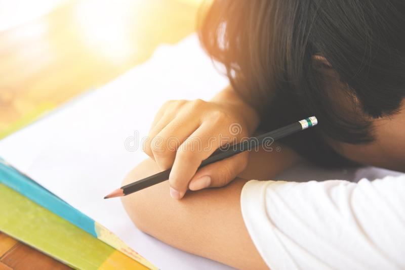 Exam stress / education young female college in class taking notes and using a pencil sitting learning concept stressed student stock image