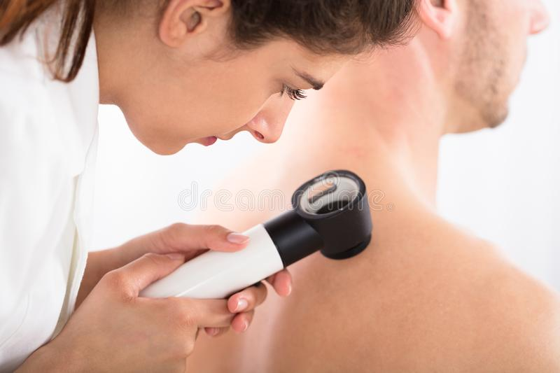 Exame da pele do doutor Using Dermatoscope For foto de stock royalty free