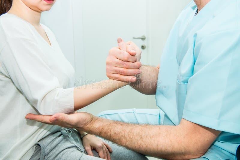 Exame físico neurológico dos reflexos das mãos O neurologista do doutor verifica o estado dos reflexos pacientes do ` s no escrit fotos de stock