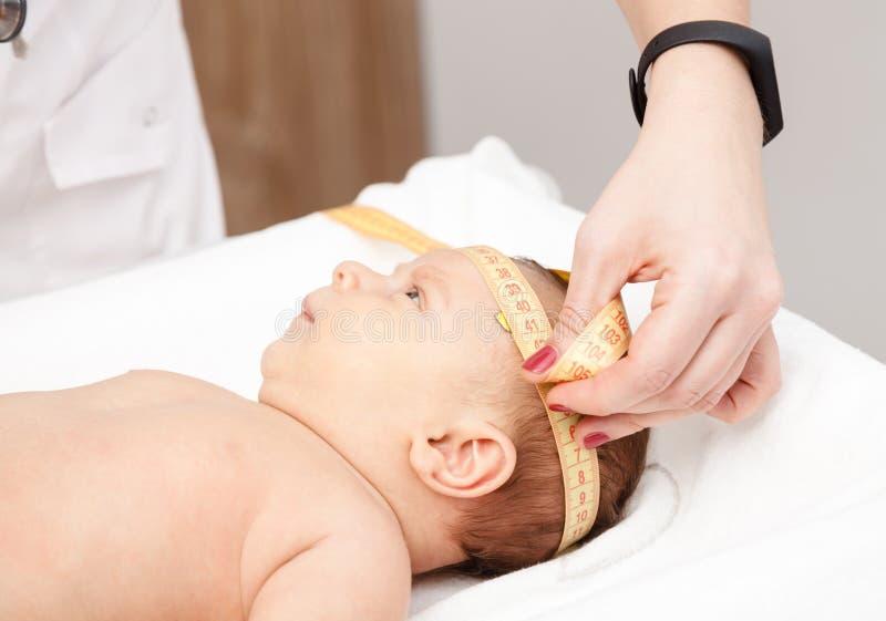 Exame médico infantil - doutor que verifica o tamanho principal com um measureme foto de stock royalty free