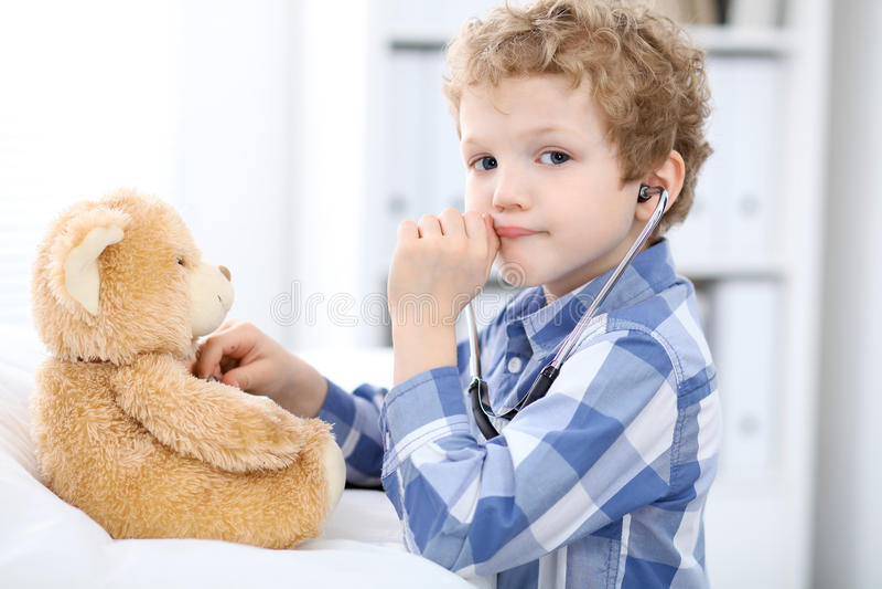 Exame paciente da saúde do afrer da criança que joga como um doutor com o urso do estetoscópio e de peluche imagem de stock