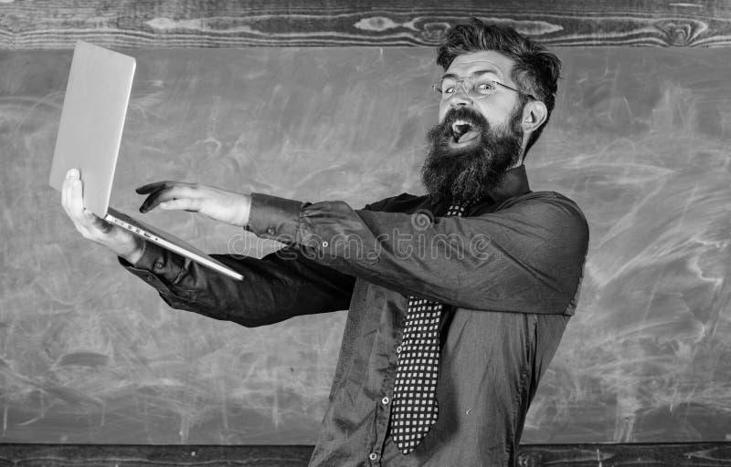 Examen acertado Pase la prueba en línea El hombre feliz barbudo del profesor con el ordenador portátil moderno pasó prueba la piz foto de archivo