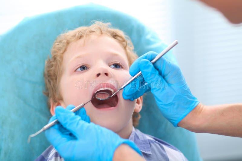 Examen de dentiste dents de petits garçons dans la chaise de dentistes à la clinique image stock