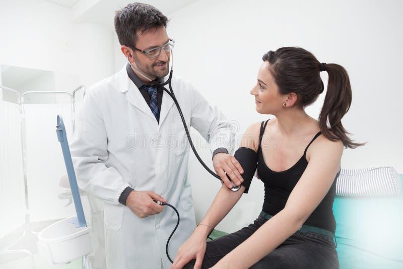 Examen del doctor de una señora joven con el estetoscopio fotos de archivo libres de regalías