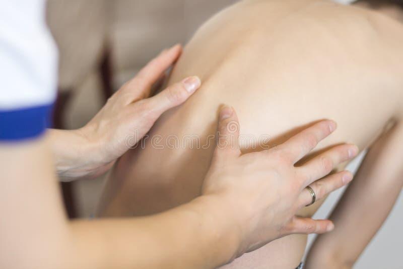 Examen du défaut d'un enfant dans la posture Les mains du docteur examinent l'épine d'un petit patient image libre de droits