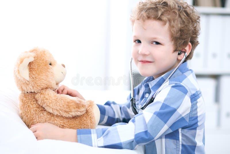 Examen paciente de la salud del afrer del niño que juega como doctor con el oso del estetoscopio y de peluche fotografía de archivo