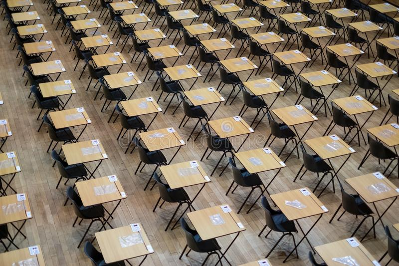 Examination hall set up with chairs and wooden desks. Photographed at Queen Mary, University of London royalty free stock photography