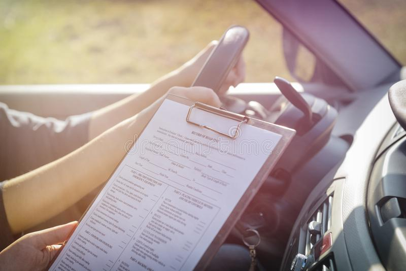 Examiner filling in driver`s license road test form royalty free stock photography