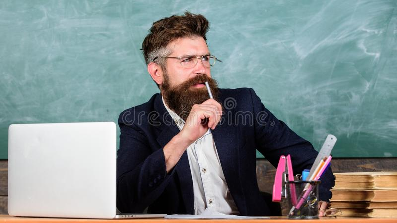 Examiner full of doubts sit at table chalkboard background. School exam concept. Tricky examinator hesitates about mark. Examiner bearded teacher with stock photos