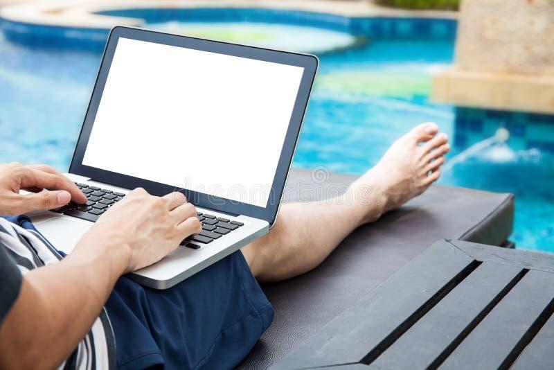 Examinez la maquette de l'ordinateur portable qu'un homme emploie dans la piscine des vacances - images libres de droits