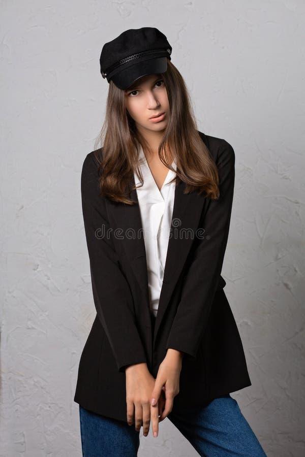 Examinez la pousse d'une jolie fille de brune posant dans le chapeau élégant, cric photos stock