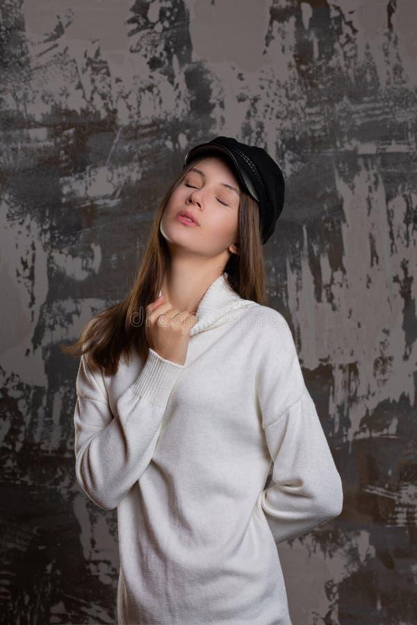 Examinez la pousse de la fille sensuelle de brune posant dans le chapeau et le kn élégants photos libres de droits