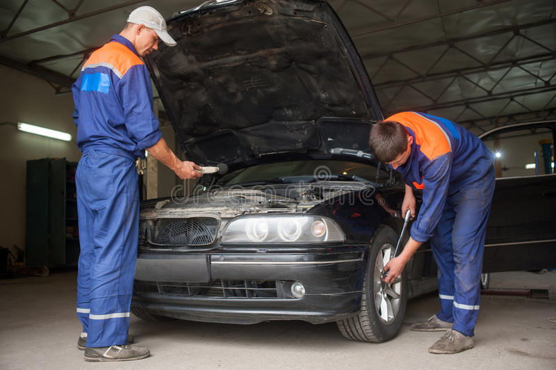 Examining car at the auto repair shop stock photos