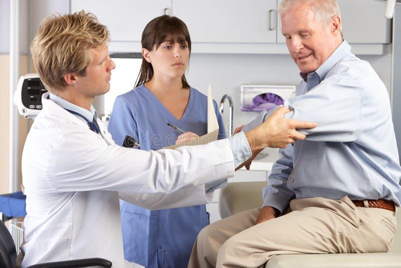 Examining Male Patient With医生手肘痛苦 免版税库存图片