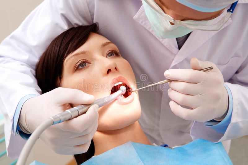 Examining oral cavity. Image of young woman keeping her mouth open while dentist examining it stock images