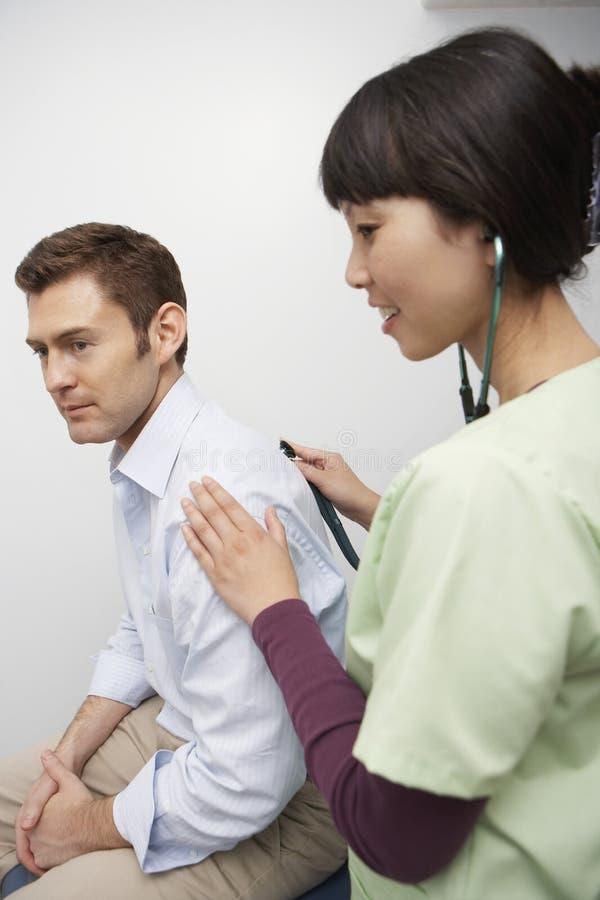 Examining Patient Using Stethoscope医生 图库摄影