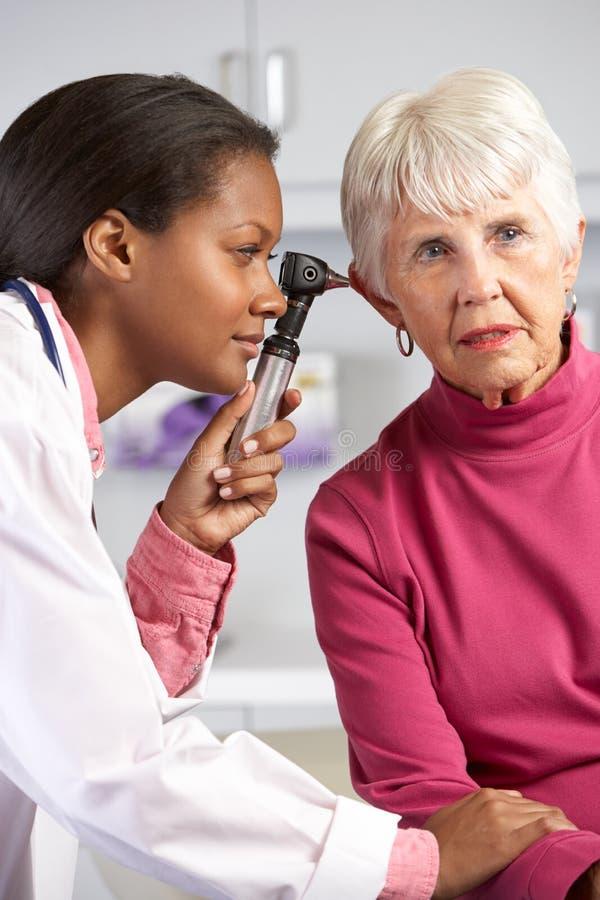 Examining Senior Female Patient医生的耳朵 免版税图库摄影