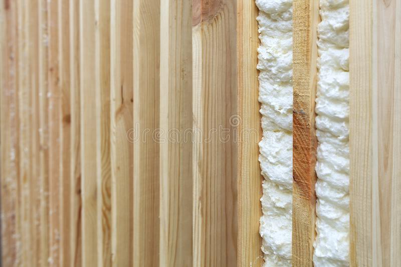 An example of filling the gap between vertical wooden planks with building foam royalty free stock photo