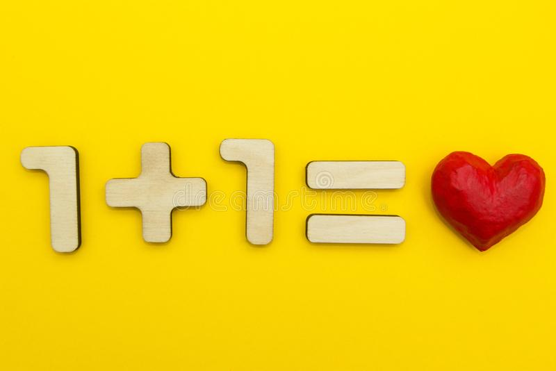 Example: one plus one equals love on a yellow background stock photo