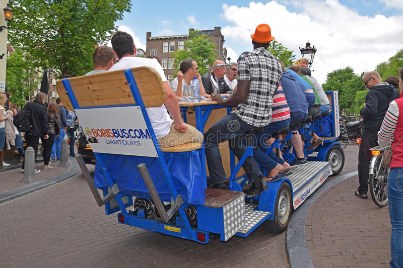 Example of Party Bike in Amsterdam with passengers having a lot of fun together. It is also known as beer bike because typically there are bar tenders onboard royalty free stock photography