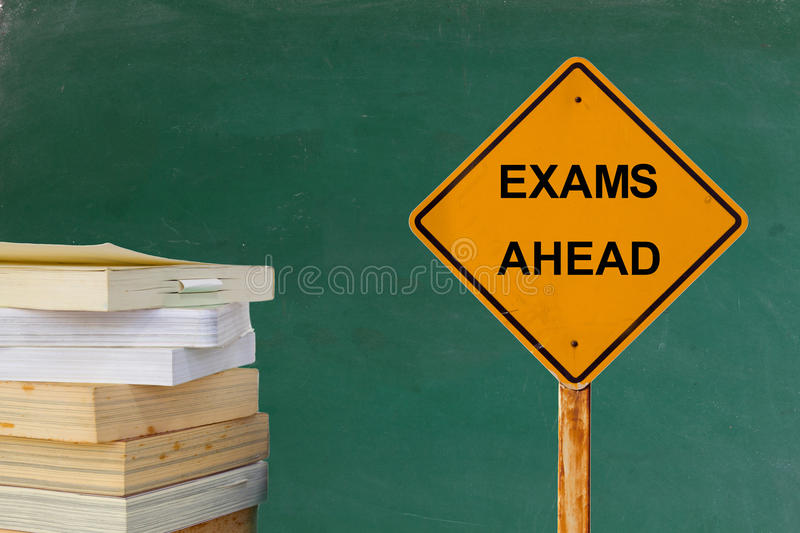 EXAMS AHEAD word on traffic sign with books and blackboard. EXAMS AHEAD message on yellow traffic sign with books and green blackboard royalty free stock images