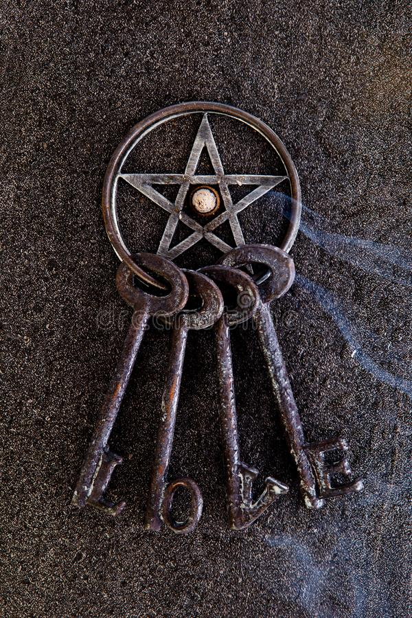 Exaspérez le burning dans le pentagone étoilé gris en métal avec le porte-clés d'amour sur le sla images stock