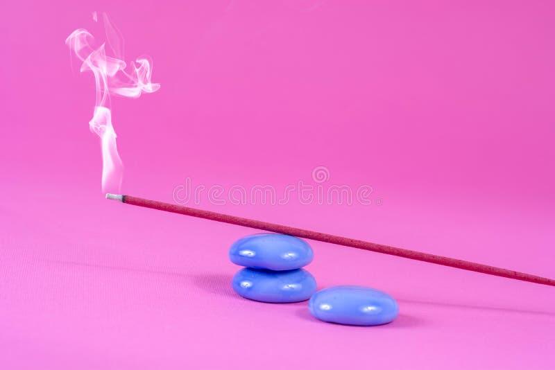 Exaspérez le burning et la fumée de bâton sur la roche bleue sur le rose photo stock