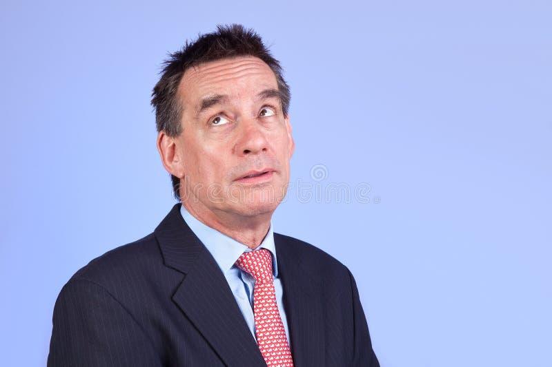 Exasperated Business Man Raising Eyes on Blue. Attractive Exasperated Annoyed Business Man in Suit Raising Eyes on Blue Background stock image