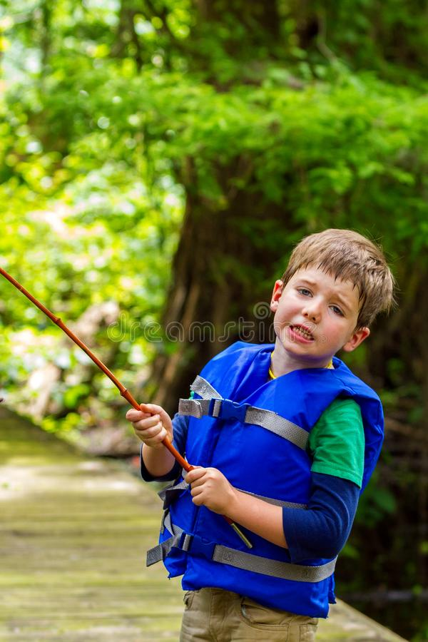 Exasperated Little Boy Looks at the Camera in Frustration Because His Fishing Pole is Caught in a Tree royalty free stock photography