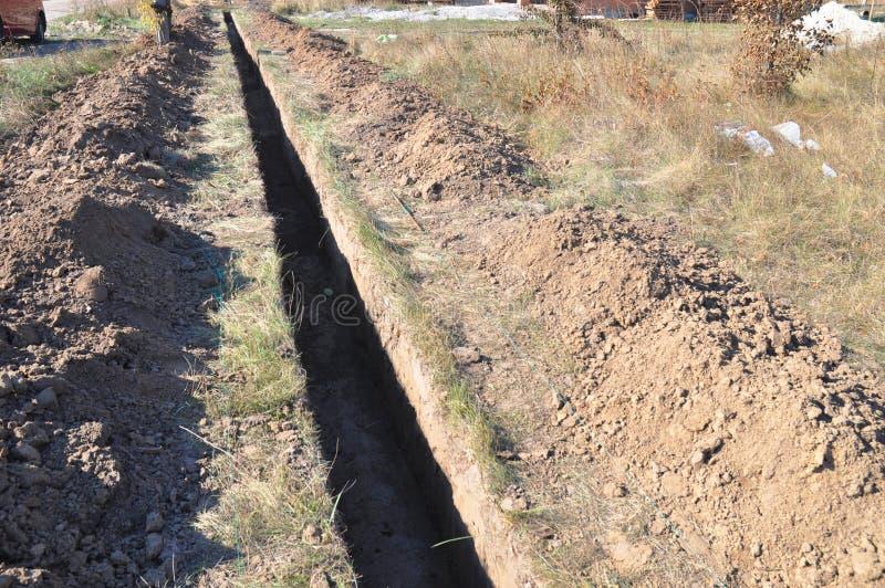 Excavación de un foso Terraplénes, foso de excavación Foso de tierra largo cavado para poner el tubo o la fibra óptica foto de archivo