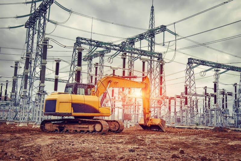 Excavador amarillo en el emplazamiento de la obra de la central eléctrica Cubo del excavador en la tierra excavada fotos de archivo libres de regalías