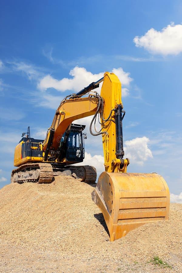 Excavador amarillo en una pila de suciedad con el cielo azul imagen de archivo