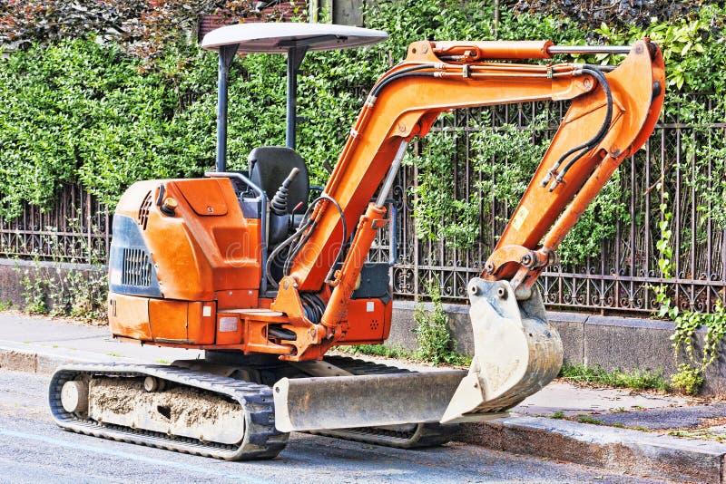 Excavador anaranjado parqueado en el borde de la carretera foto de archivo