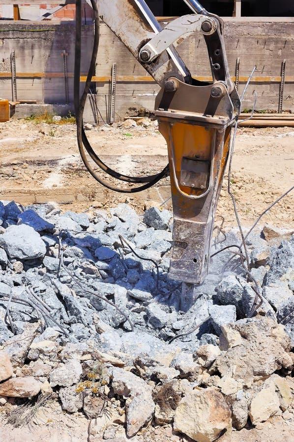 Excavador con el martillo hidráulico que rompe el hormigón fotografía de archivo