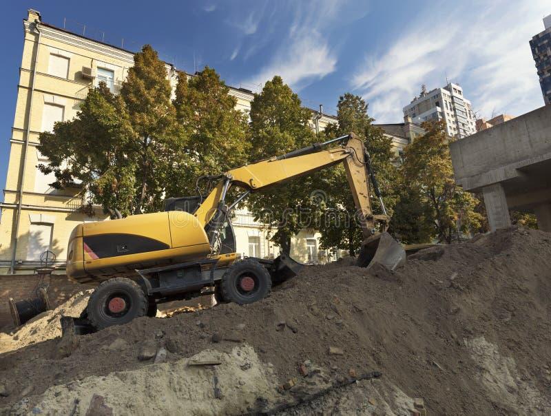 Excavador de la construcción pesada durante la construcción de un camino y de un nuevo edificio de varios pisos foto de archivo libre de regalías