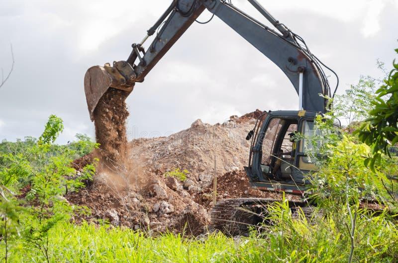 Excavador Empting Dug Dirt imagenes de archivo