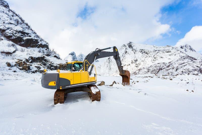 Excavador en las montañas nevosas foto de archivo libre de regalías