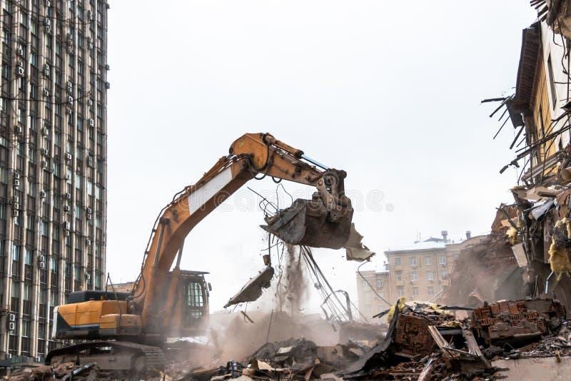 Excavador hidráulico de la trituradora que trabaja en un sitio de demolición fotos de archivo libres de regalías