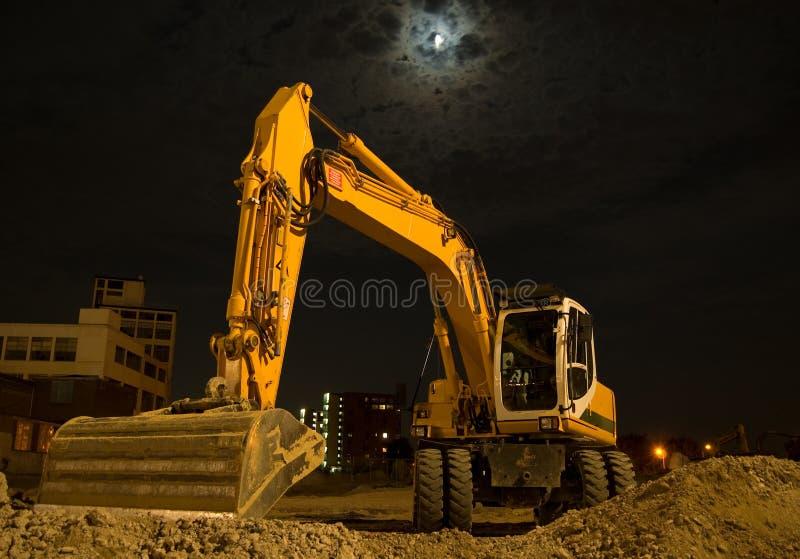 Excavador por noche fotos de archivo