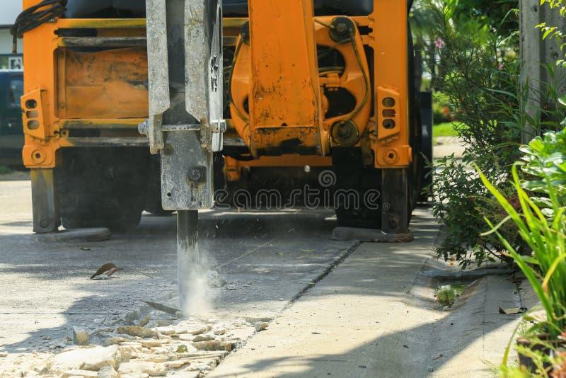 Excavador que rompe la superficie de la carretera concreta imagenes de archivo