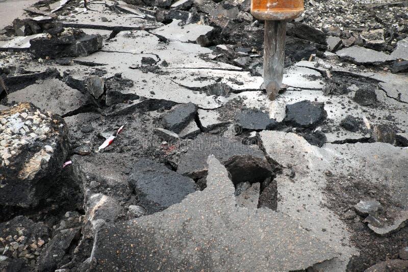 Excavador que rompe la superficie de la carretera concreta con el taladro del hydrohammer imágenes de archivo libres de regalías