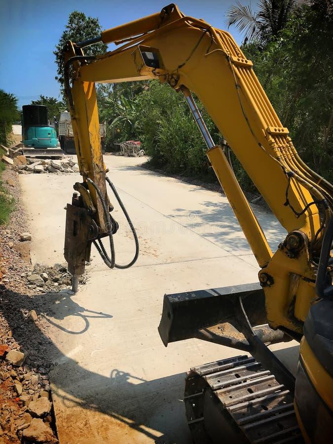 Excavador que rompe y que perfora el camino concreto para reparar fotos de archivo libres de regalías