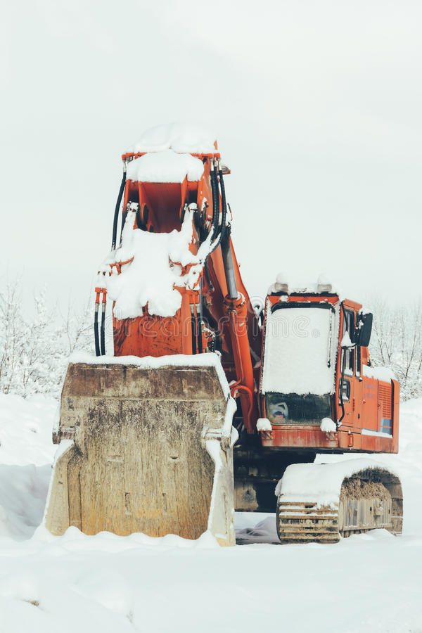 Excavador que se coloca en el invierno de la nieve al aire libre, primer fotografía de archivo libre de regalías