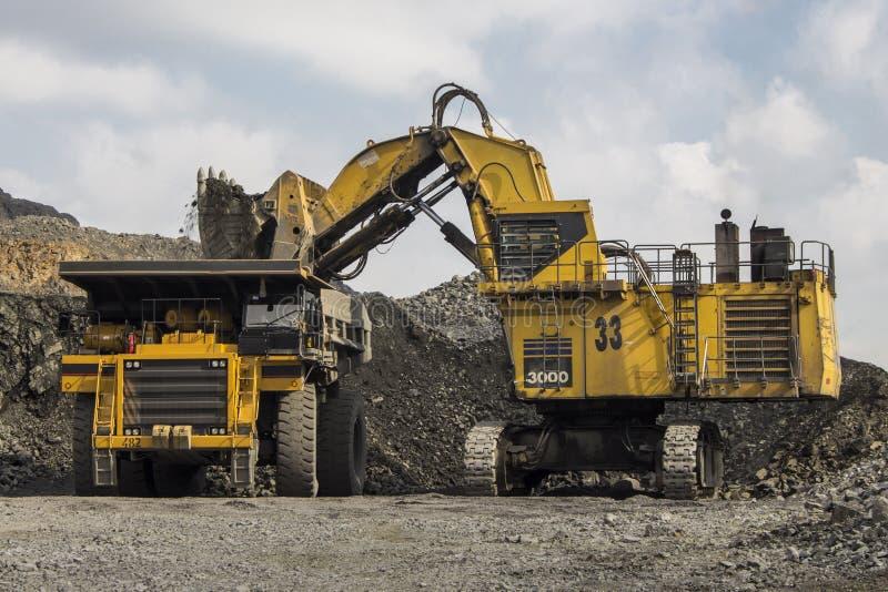 Excavador y camión en la mina del hierro imagen de archivo
