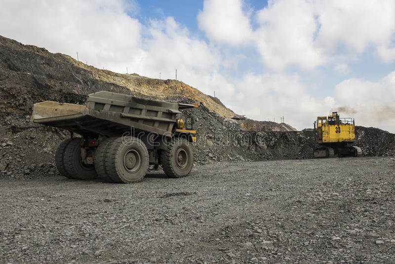 Excavador y camión en la mina del hierro imágenes de archivo libres de regalías
