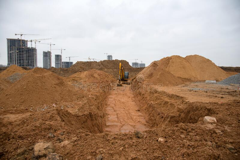 Excavadora excava una trinchera grande para la colocación de tuberías Retroceso durante el movimiento de tierra en el lugar de co fotos de archivo libres de regalías