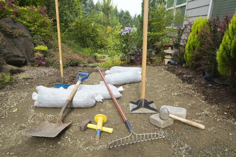 Excavando y poniendo las pavimentadoras para el patio del jardín fotografía de archivo