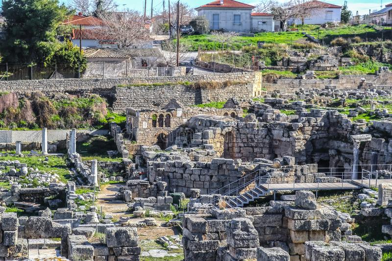 Excavated archaeological ruins in Ancient Corinth Greece with stairs and walkway for tourists and red tile roofed village houses. Behind stock photography