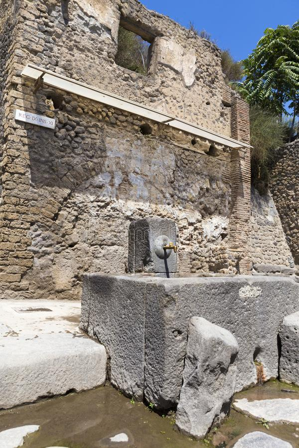 The excavated and preserved fountain in Pompeii. The excavated and preserved fountain from where the tourists can drink in Pompeii from Italy royalty free stock images